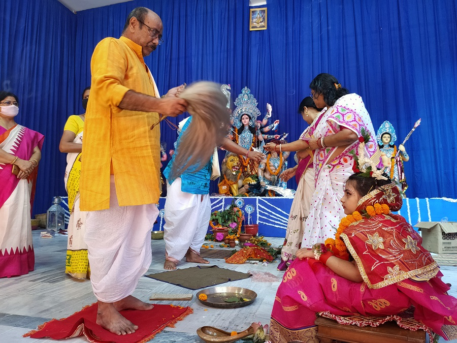 The priest performs a ritual of Kumari Puja on the occasion of Maha Astami at Deshpriya Club.