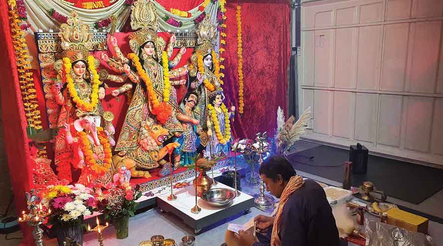 Priest Proloy Mukherjee performs the puja at the garage of one of the trustees of Sankalpo in Chelmsford, Essex,  on Saturday.