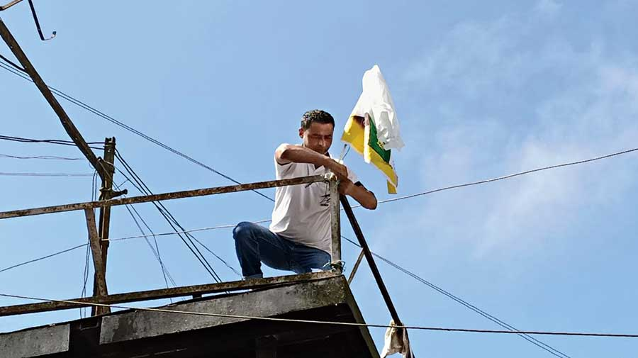 A Gurung supporter hoists the Morcha flag atop the podium at Chowk Bazar in Darjeeling on Saturday.