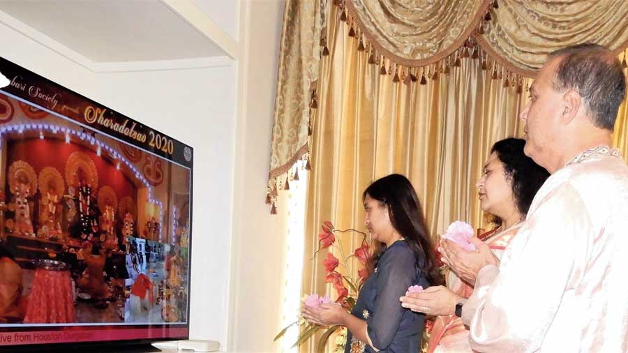 A family in Houston offers anjali in front of a TV streaming the Durgabari proceedings.