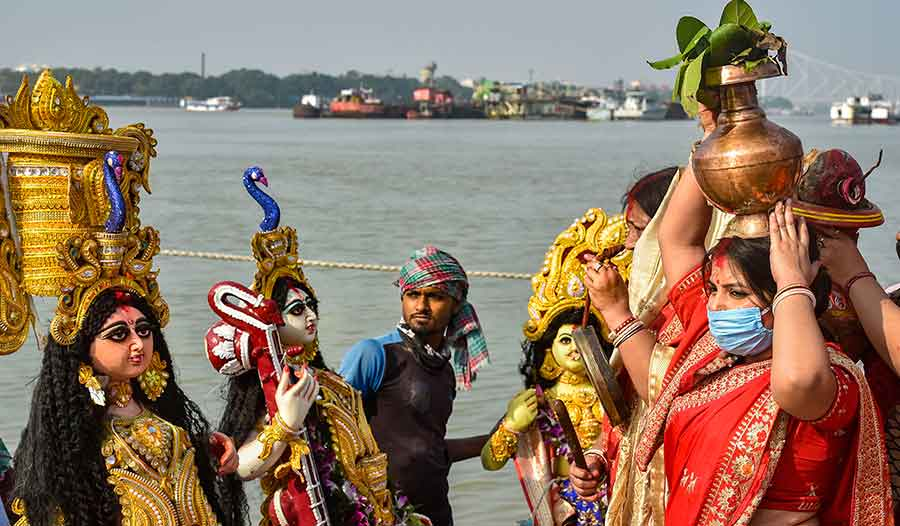 Devotees immerse an idol of Goddess Durga in Ganga river on the last day of Durga Puja festival, in Calcutta, Monday, October 26, 2020.