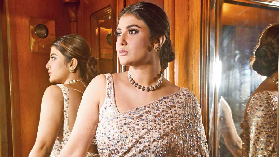 """Parno was party-ready in this Tequela Rose by Pooja Prassad sari. Mainak gave her beautiful mauve smokey eyes, glossy lips and a bun. """"The Amrapali Jaipur neckpiece had pearls on one side and was multicoloured on the other. The sari had holographic shades, which it matched well with,"""" said Ankita."""