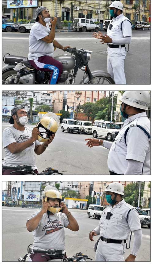 A policeman makes a motorcyclist at the Park Circus seven-point crossing wear a helmet on Monday.