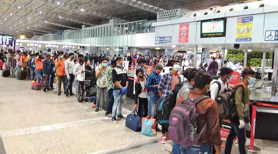 A queue of passengers for security check extends till  the airport's terminal building entry gate on Tuesday