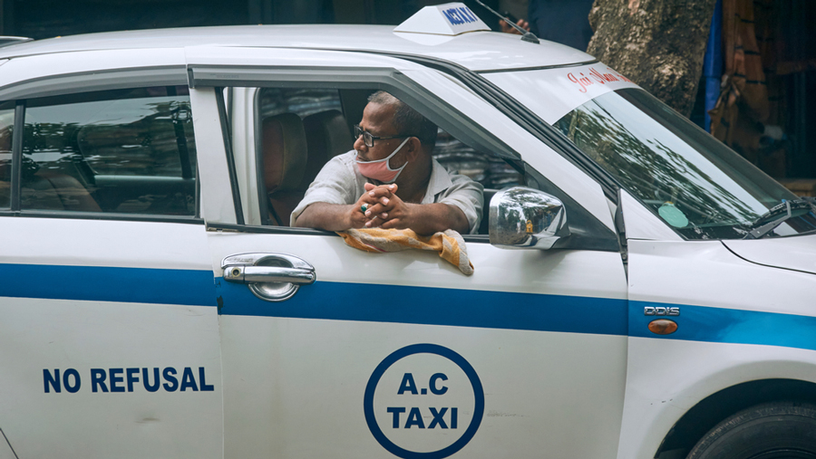 A cab driver looks through his taxi window, parked at a roadside in Kolkata.