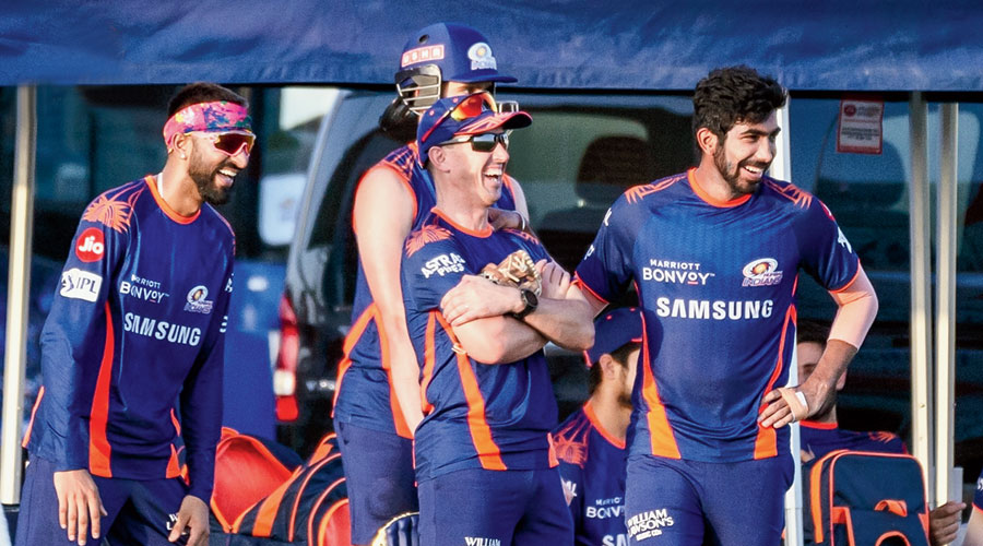 Krunal Pandya (left) and Jasprit Bumrah (right) share a light moment with a support staff member during Mumbai Indians' practice on Saturday.