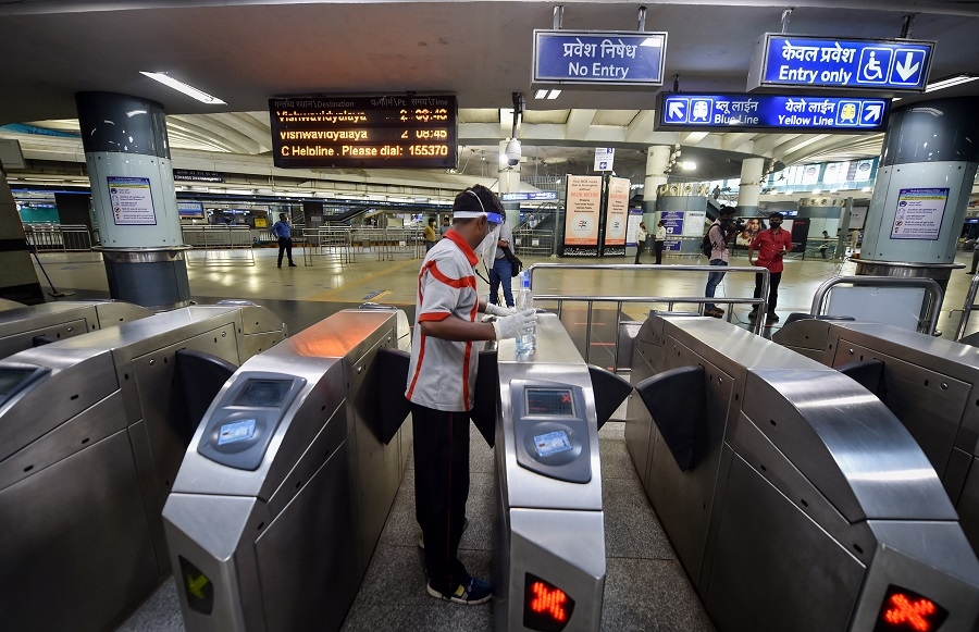 A worker sanitises entry gates at Rajiv Chowk station in New Delhi on Monday.