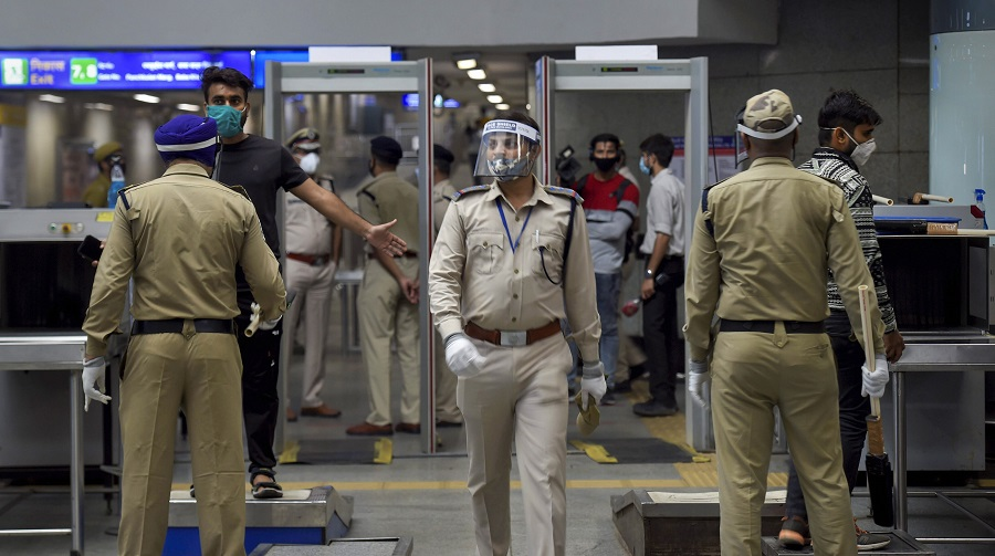 A commuter undergoes checking as security personnel patrol Rajiv Chowk station in New Delhi on Monday.
