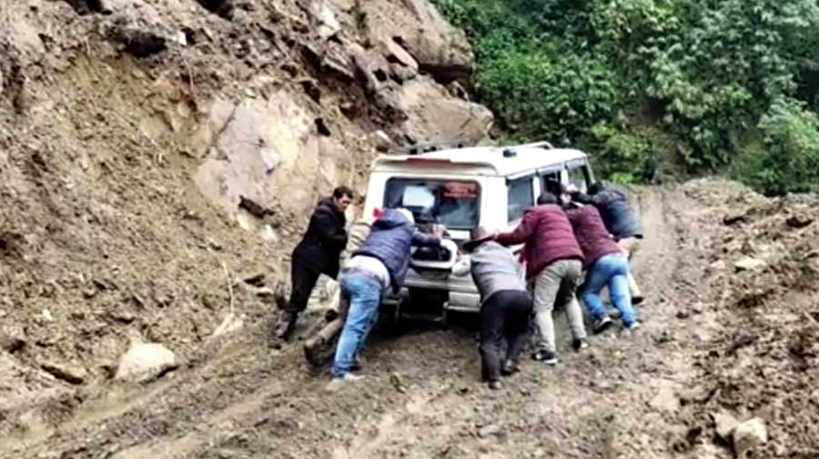 A car being pushed after it got stuck on the Daparijo road in Arunachal.