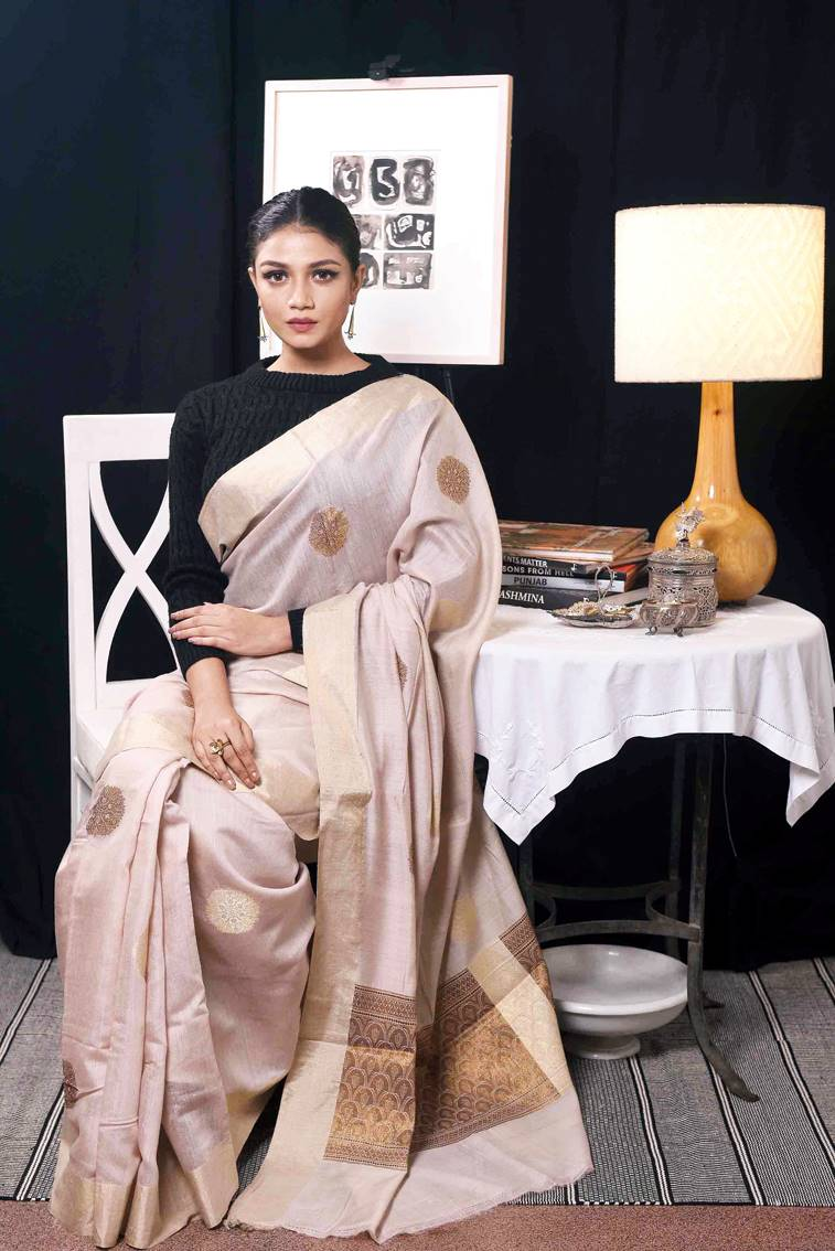 Look 4: Muga silk Benarasi sari with zari Woven by hand from yarn by a master craftsman in Benares, this rich ivory muga silk in its natural colour is embellished with gold and copper-hued zari. Intentionally without an ornate border or all-over body, the simplicity of the design keeps it elegant yet regal. This is paired with floral earrings and a floral ring, which are handcrafted from an alloy of half silver and half bronze.