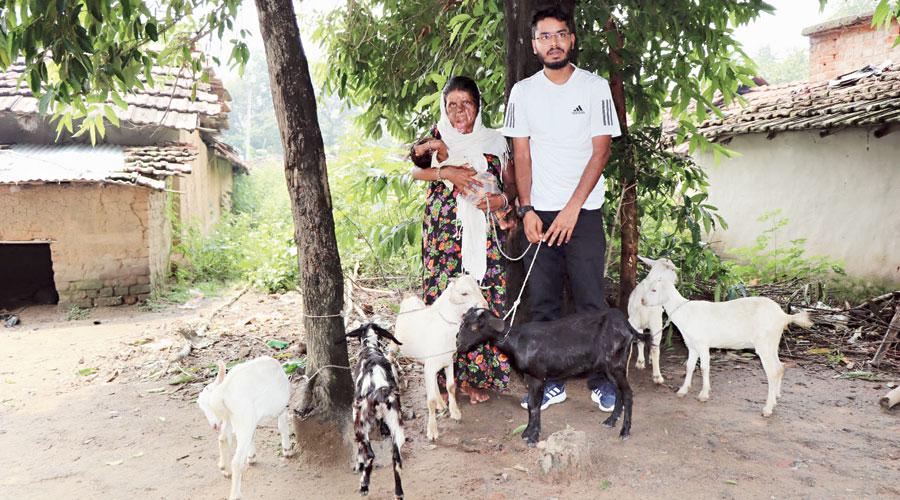 Deepak Kumar (right) hands over goats to the Lakhi Muni at Topchanchi block of Dhanbad.