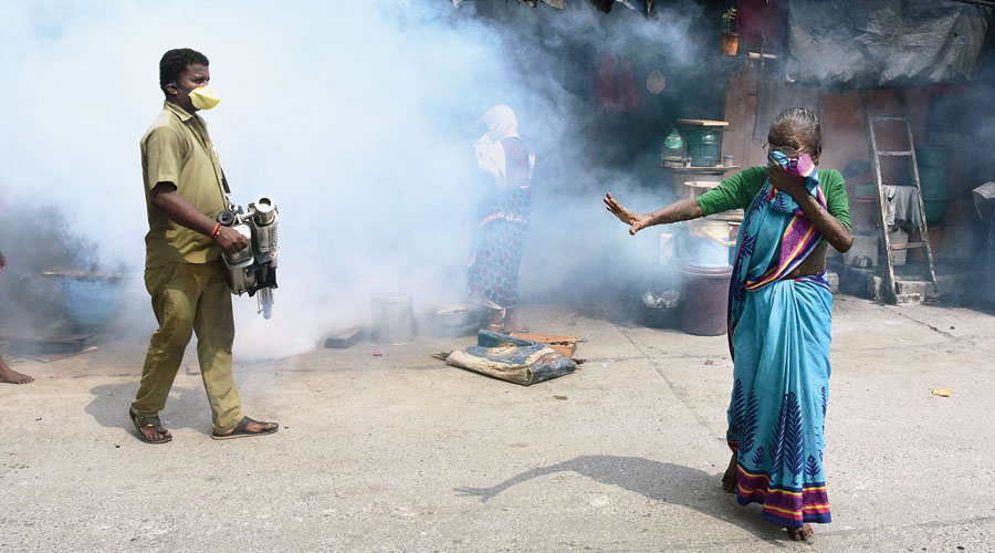 A BMC worker carries out fumigation at Rey Road area in Mumbai on Friday.