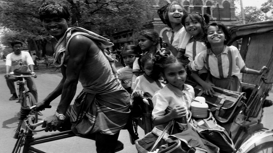 File picture of children on their way to school on a rickshaw