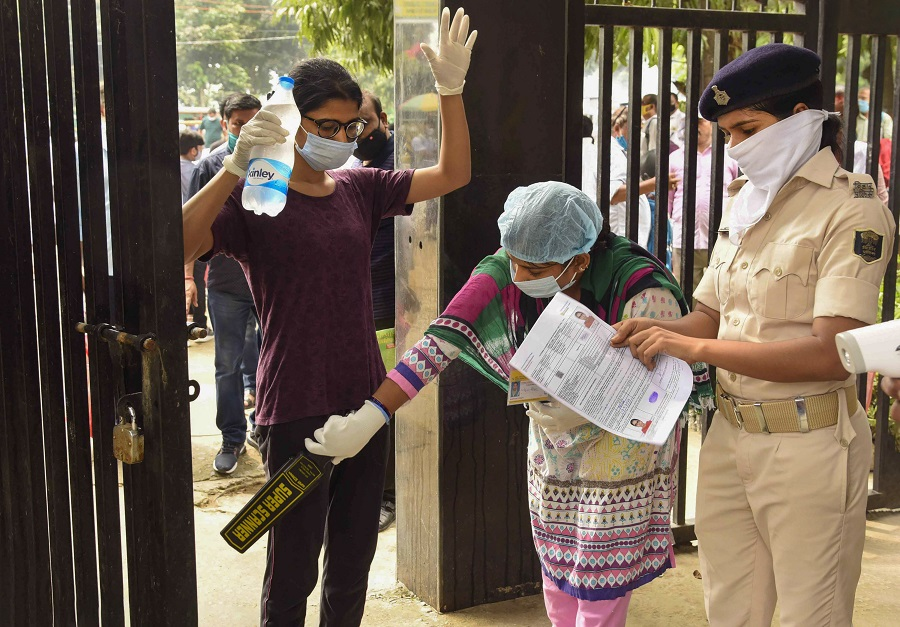 Candidates undergo a security check before entering an examination centre for the National Eligibility-Cum-Entrance Test (NEET), during unlock 4.0, in Patna, Sunday, Sept. 13, 2020.