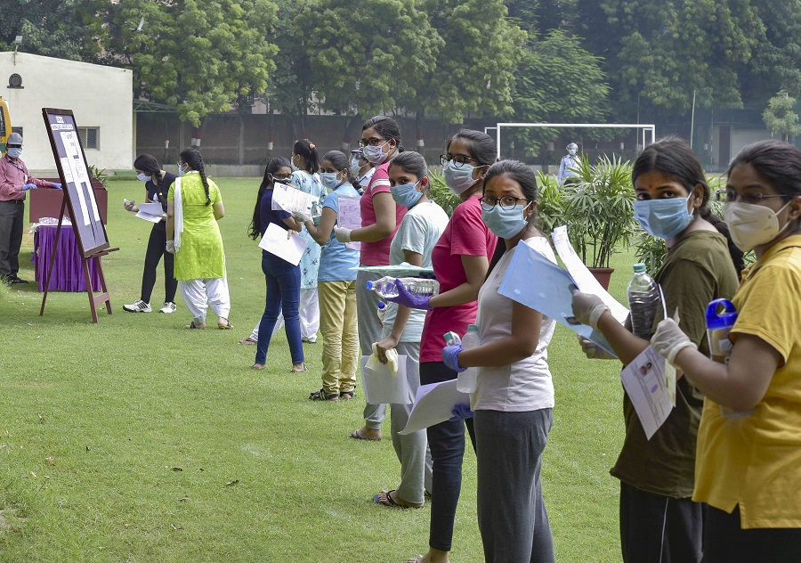 Aspirants wearing masks stand in a queue at an examination centre for National Eligibility cum Entrance Test (NEET), in New Delhi, Sunday, Sept. 13, 2020.
