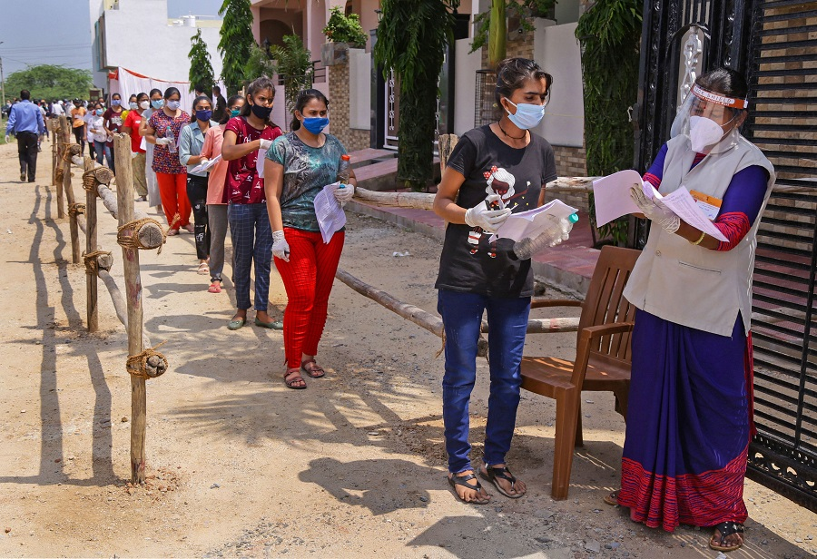 Candidates wearing masks stand in a queue at an examination centre before appearing for the National Eligibility cum Entrance Test (NEET) during unlock 4. o, in Beawar, Sunday, Sept. 13, 2020.