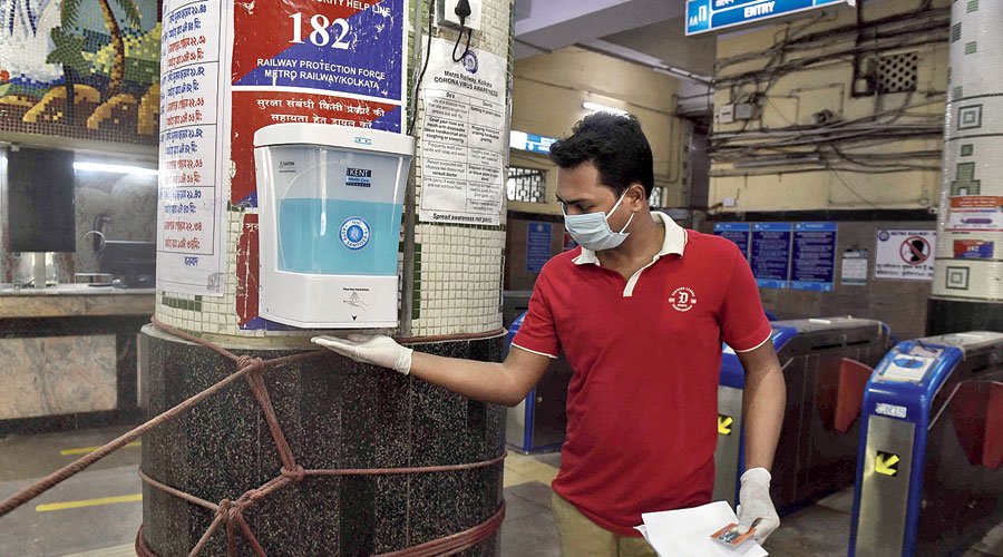 A candidate takes sanitiser from a dispenser at the station