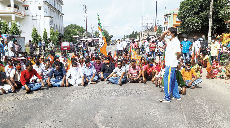 BJP workers and leaders raise a roadblock at Goghat in Hooghly on Sunday.