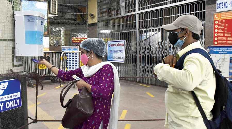 A passenger takes sanitiser from a dispenser at Dum Dum Metro station
