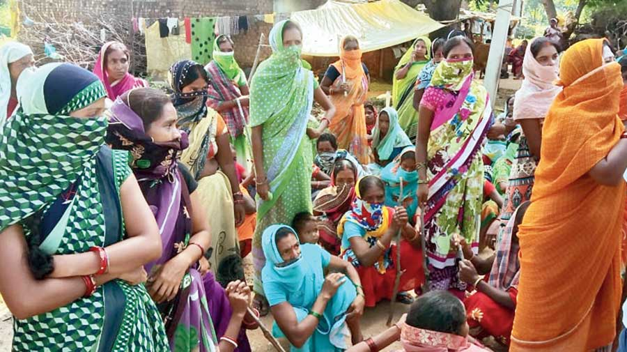 Women gather in the village after police reach there to collect the details of the lynching.