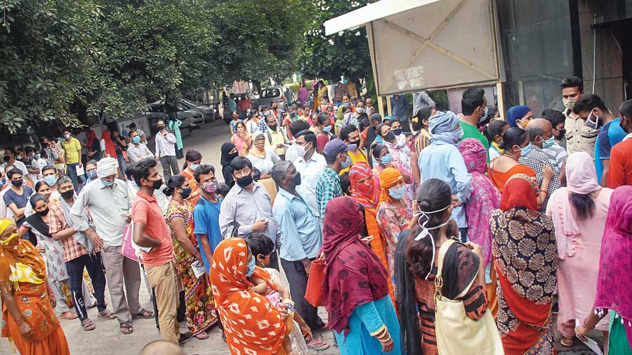 People wait outside the district hospital OPD in Noida on Monday. Coronavirus has put a strain on the country's rural healthcare services, including maternity care.
