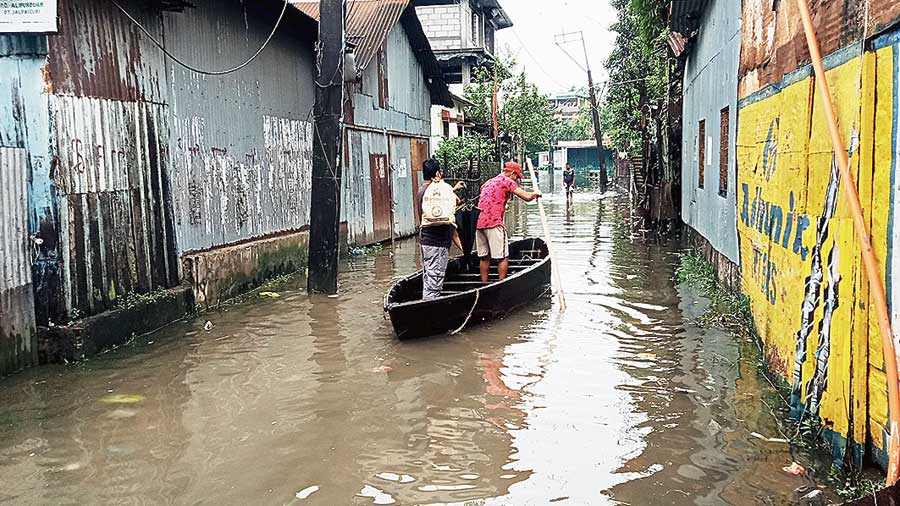 Residents row a boat at a submerged locality in Alipurduar on Tuesday.