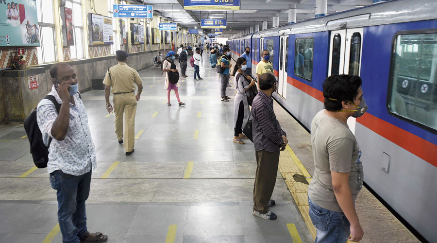 Commuters maintain distance among themselves while waiting to board a train at Dum Dum Metro station on Tuesday morning.