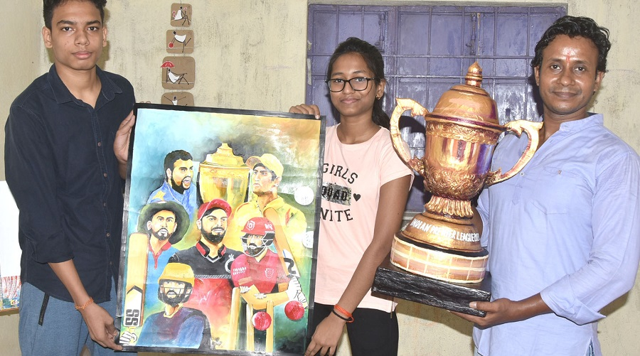 Art teacher Arjun Ram Paul and his students, Aditya Singh (left) and Vinita Mandal with their painting and the IPL 2020 trophy.