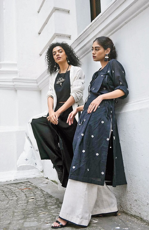 "5. This black-and-white jamdani collection is all about the magic of mix-and-match layered with plenty of campus crispness. Subhamita's white jamdani throw paired with a crop top and a pair of palazzo is Sayantan's ode to jackets. ""I love jackets as it does the trick for the entire outfit. It is an interesting interplay of structure and form,"" says Sayantan, who fell in love with jackets after his visit to Italy. Black patent brogues, silver earrings and a heavy silver neckpiece complete the ""simple yet dramatic"" look. Olivia will keep this one aside for a sundowner. Bibriti's angarkha-style black-and-beige jamdani kurta is striking. ""The neckline is made interesting with a fold of a fabric. You can wear it as a dress too,"" says Sayantan. Bibriti sports it with structured pants, golden tasselled earrings and black stilettos. The heritage backdrop of the Currency Building complements the languid modernity of the silhouettes."
