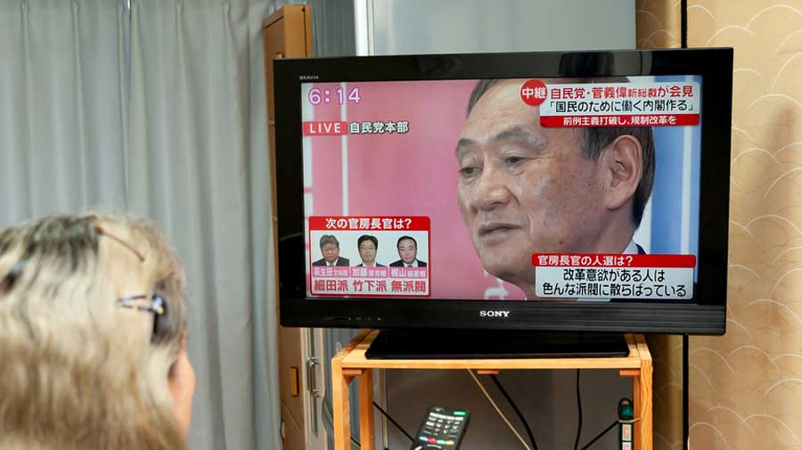 A woman watches a news conference broadcast on Japanese television featuring Yoshihide Suga.