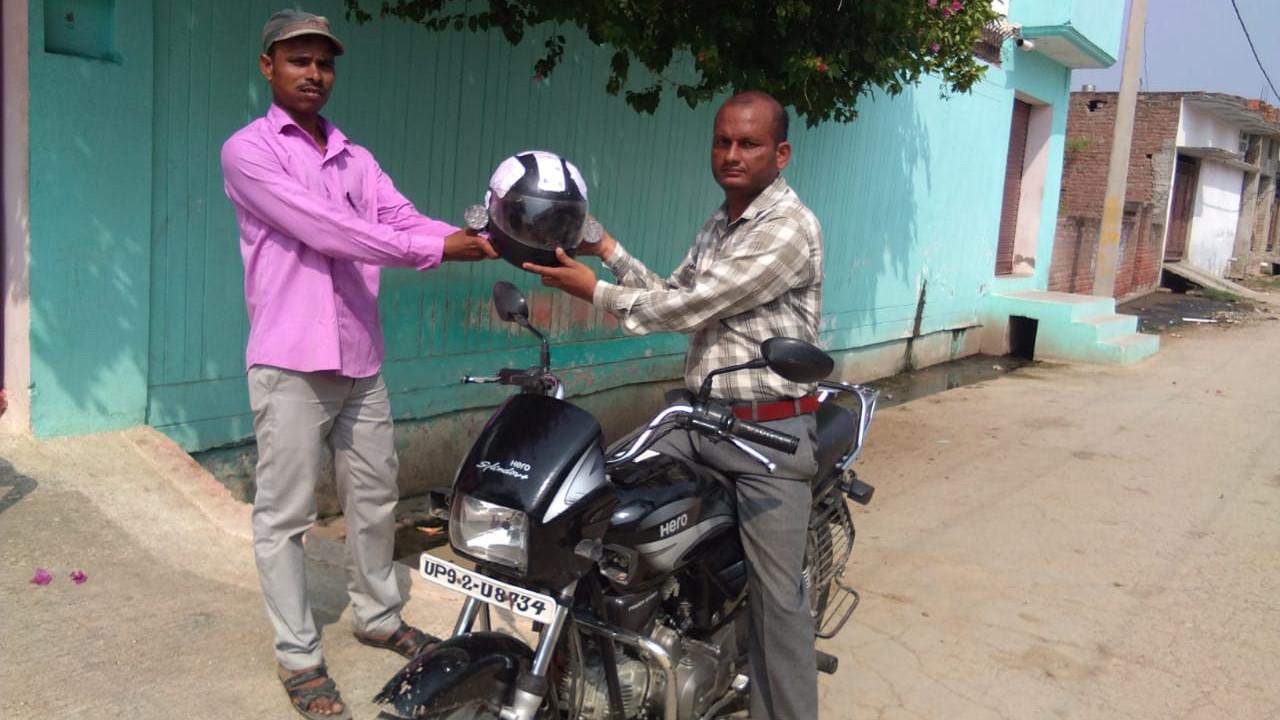 Dinesh Kumar takes the devise-fitted helmet from his friend before starting his bike in Jalaun, Uttar Pradesh on Wednesday.