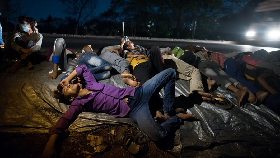 Migrant workers sleep on the highway on their journey back home during the  nationwide Covid-19 lockdown, May 9, 2020.