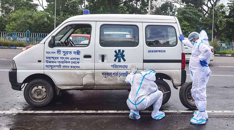 Health workers change a flattened tyre of an ambulance as they transport a Covid patient to a hospital, in Calcutta, Sunday, September 13, 2020.