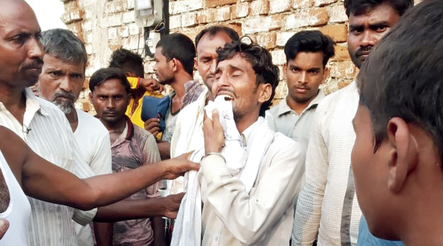 The deceased couple's son Jitendra Paswan in tears outside their house in Garhwa on Friday