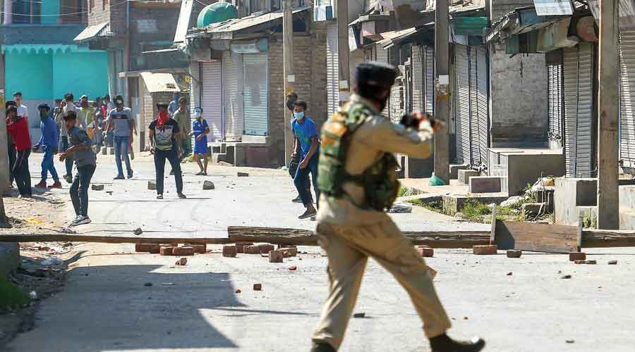 A security official tries to stop protesters from throwing stones after the encounter in Srinagar on Thursday