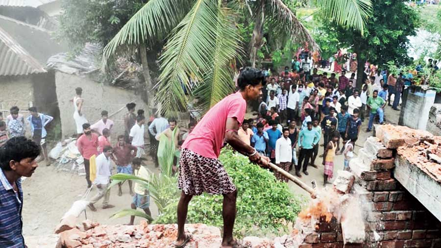 Villagers demolish the house of one of the accused in youths at Galsi on Friday.