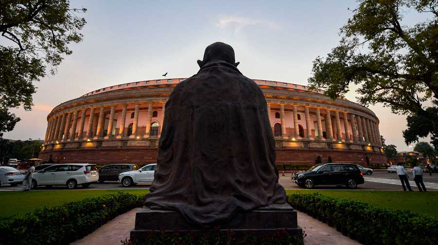 The Mahatma Gandhi statue in the backdrop of Parliament House on the opening day of monsoon session in New Delhi.