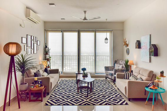 A monochrome living room designed by Tanya Sen with some vibrant furniture, plants and a black-and-white-patterned carpet