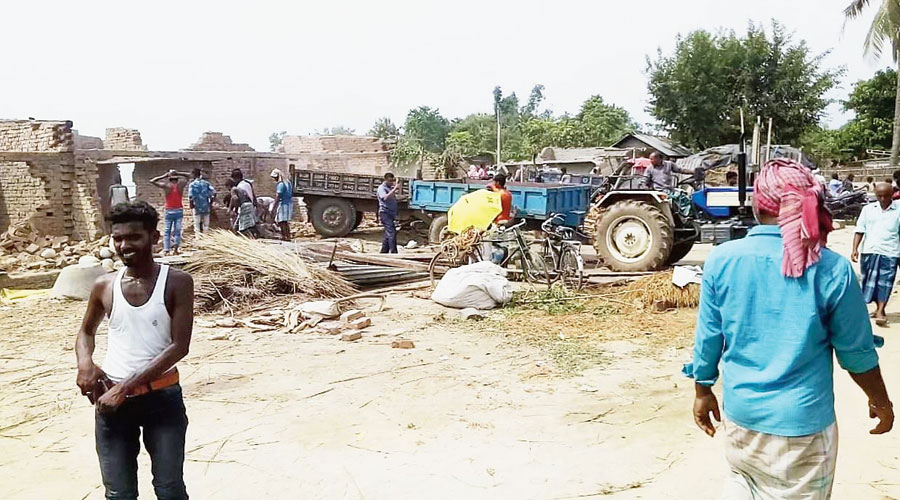 Residents dismantle houses before the Ganga devours them to salvage bricks, iron rods, grills and other items at Baishnabnagar in Malda.