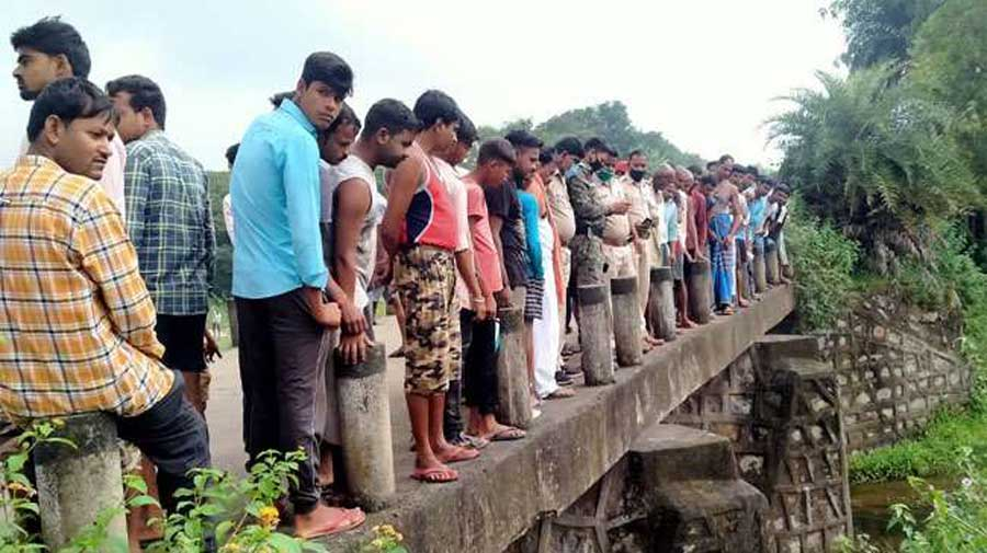 Villagers near the spot where the dead body was found in a river in Koderma on Tuesday.
