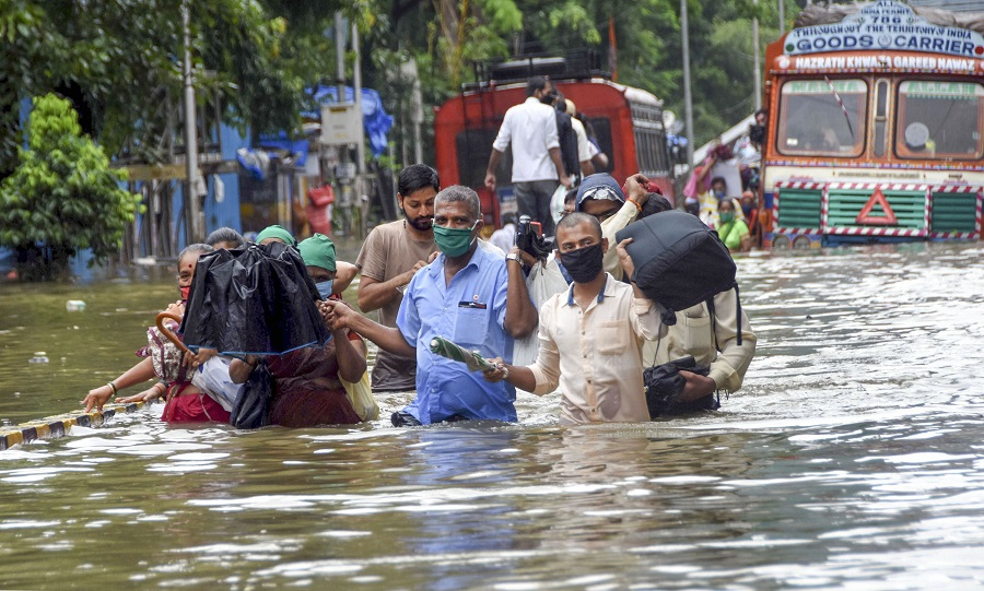 People wade through a waterlogged street at Parel area in Mumbai on Wednesday.