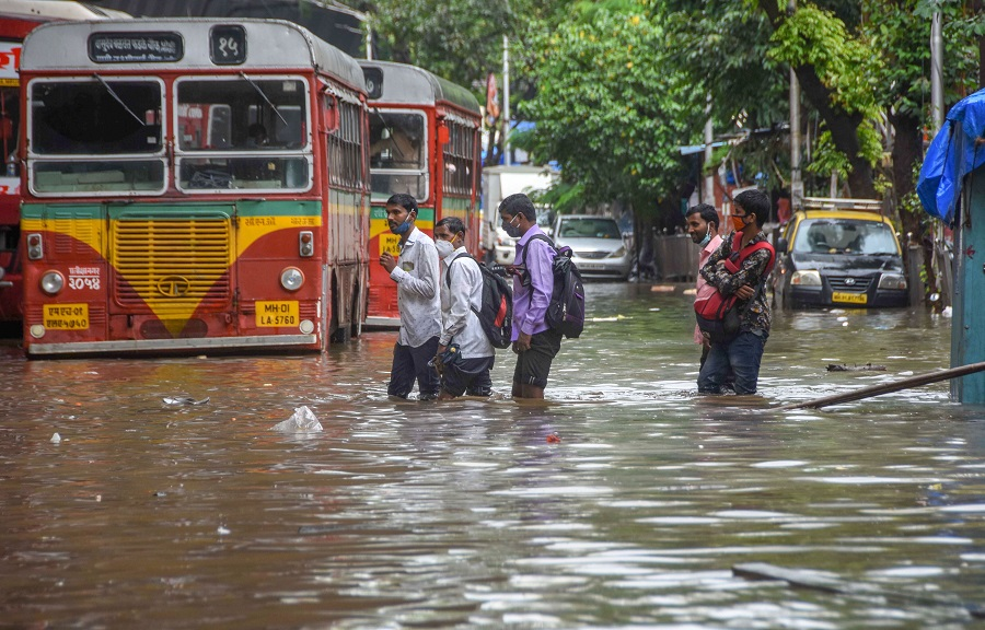 People wade through a waterlogged street at Lalbaug-Parel are in Mumbai on Wednesday.