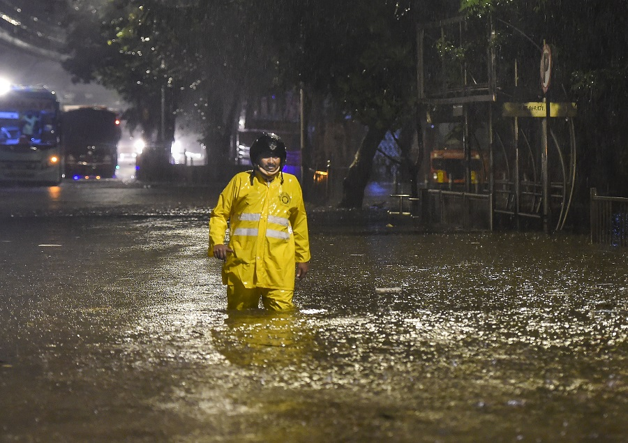 A policeman wades through a waterlogged street after heavy monsoon rain at Sion in Mumbai, on the wee hours of Wednesday.