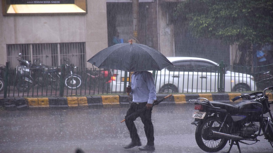 One umbrella can barely protect this pedestrian from the heavy showers at Bistupur in Jamshedpur on Wednesday