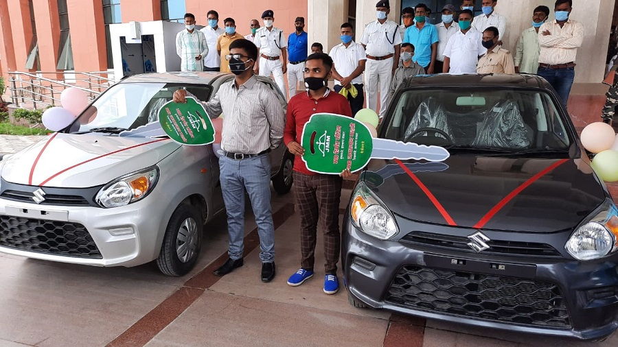 Inter science topper Amit (left) and matric topper Manish along with the cars they were gifted by education minister Jagarnath Mahto in Ranchi on Wednesday