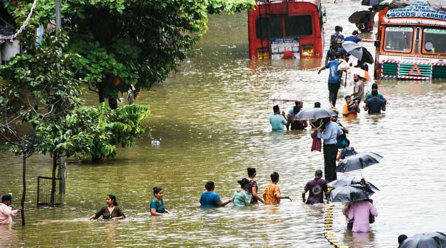 People wading through a waterlogged street in Mumbai on Wednesday