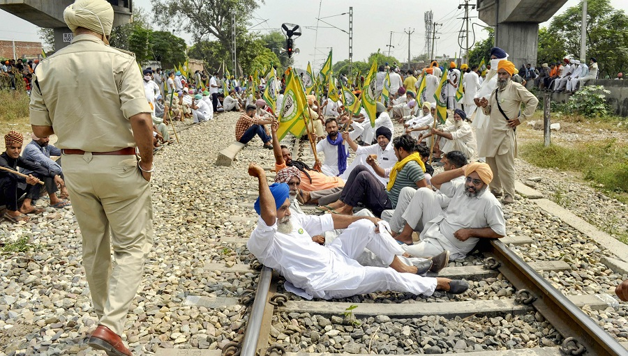 Members of various farmer organizations block a railway track during a protest against the central government over agriculture related ordinances, in Patiala on Thursday.
