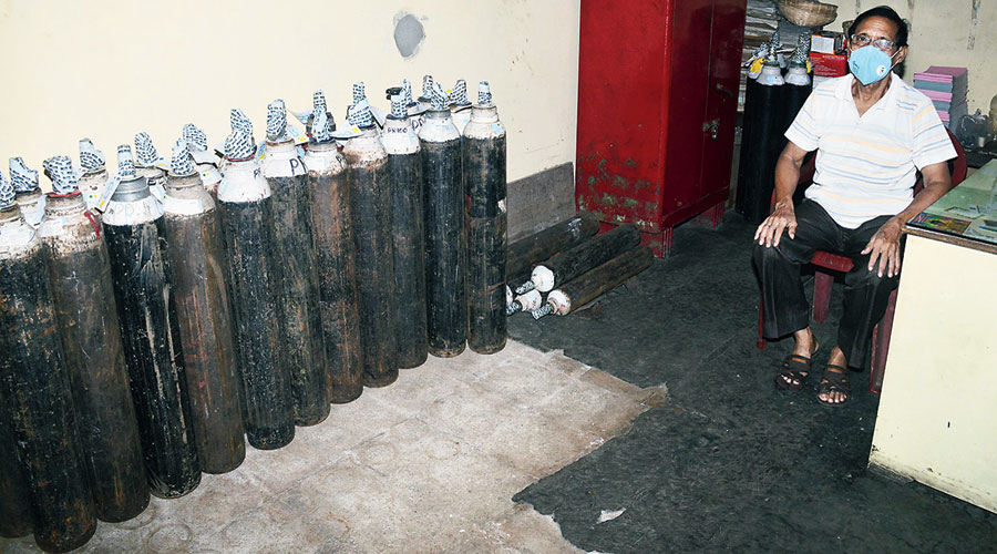 An attendant sits next to oxygen cylinders at Prasanthi Enterprises in DL Block.