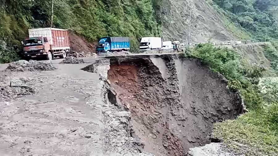 Trucks move along the damaged stretch of NH10 at Swetijhora on Thursday