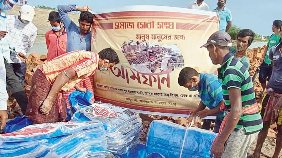 Ballygunge Samaj Sebi Sangha members distribute relief material in the Amphan-affected Sardar Para village in June.